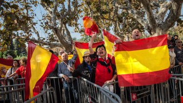 People wave Spanish flags as they protest outside the Parliament of Catalonia during a parliamentary session to pass the start of the independence process on Monday in Barcelona.