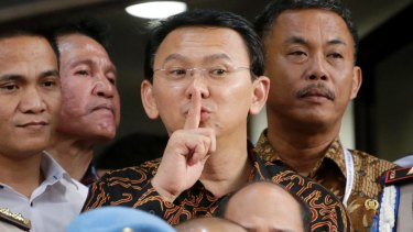 Jakarta Governor Basuki Tjahaja Purnama, popularly known as Ahok, centre, gestures to the media as he leaves after being questioned by investigators at the National Police Headquarters in Jakarta last month.