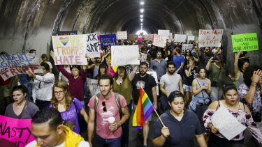 Demonstrators hold signs while marching through the Third Street tunnel during a protest in Los Angeles.