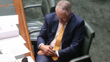 Prime Minister Malcolm Turnbull checks his Apple watch during question time.