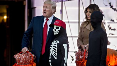 US President Donald Trump and First Lady Melania Trump celebrate Halloween with children in the White House on the same day as the Russia probe began claiming scalps.
