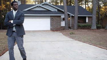 A reporter walks from the house in Jonesboro, south of Atlanta, where the boy was found.
