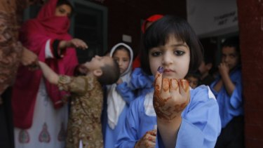 A Pakistani student shows her finger marked with ink to confirm she received a polio vaccine in Peshawar in April.