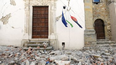 Rubble surrounds a building as a European Union flag hangs following an earthquake in Amatrice, Italy.