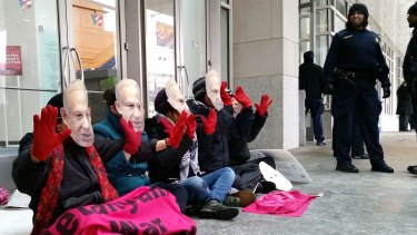 "Demonstrators wear masks bearing the likeness of Israeli Prime Minister Benjamin Netanyahu and hold up ""bloody"" hands  outside the Washington Convention Center, which is hosting the American Israel Public Affairs Committee (AIPAC) annual policy conference."