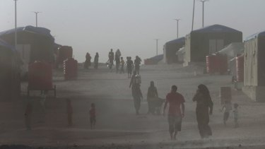 Displaced people who fled the battle between US-backed Syrian Democratic Forces and IS in Raqqa, walk in the dust at a refugee camp.