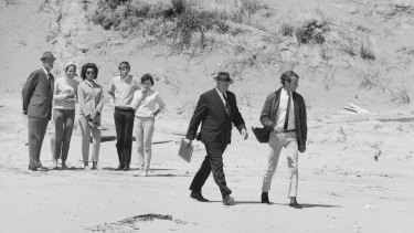 Alan Stewart, who was with Harold Holt on the day he went missing, walks along Cheviot Beach with Commonwealth policeman A Jackman.