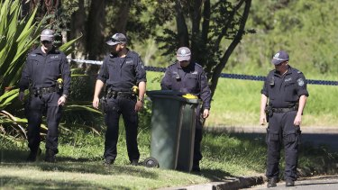 Police officers look for evidence close to a house after a 15-year-old boy was shot in the head at a home.