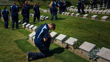 A NSW student on the schools tour of Gallipoli kneels in front a grave stone at Shrapnel Valley Cemetery.