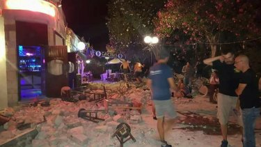 A man lies on the ground as other tourists stand outside a bar after an earthquake on the Greek island of Kos early on Friday.