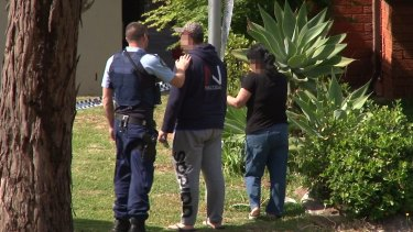 A distraught friend or relative is comforted at the scene in Sturt Avenue on Tuesday.