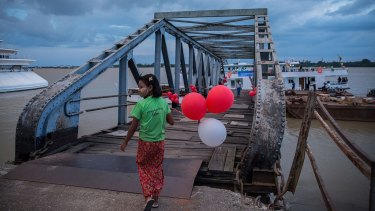A girl holds balloons at the pier in Yangon ahead of Myanmar's landmark November 8 election.