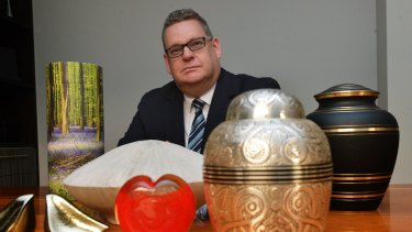 General manager of Tobin Brothers funerals Nick Fogarty with modern urns.