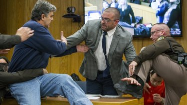 Randall Margraves, father of three victims of Larry Nassar, lunges at the disgraced doctor (bottom right) during a sentencing hearing.