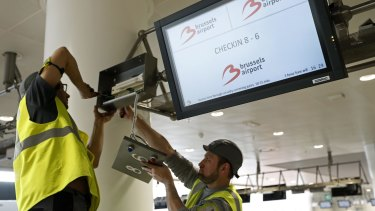 Workers repair a screen in the departures hall at Zaventem Airport in Brussels.