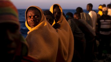 Men rescued from boats coming from Libya stand on the deck of a rescue vessel in the Mediterranean in June.