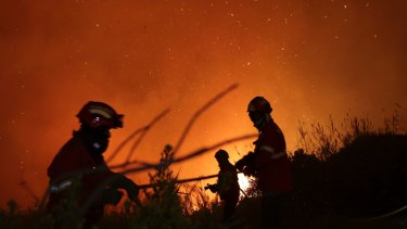 Firefighters battle a wildfire raging near houses on the outskirts of Obidos, Portugal, in the early hours of Monday.