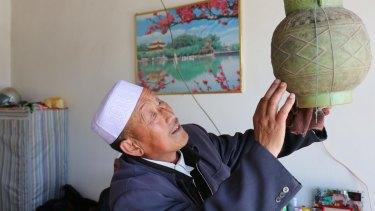 Hai Zhengjun, 64, uses a plastic vessel to take showers.