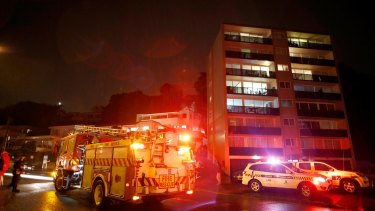 Emergency services work below a nearby hillside after it collapsed and fell onto apartments in Auckland on Tuesday night.