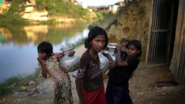 Rohingya Muslim girls carry water pots in Kutupalong refugee camp in Bangladesh.