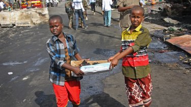 Somali children assist the effort to clear the bomb scene in Mogadishu by carrying away unidentified charred human remains in a cardboard box.