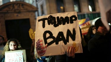 A man holds a placard during a gathering in Paris to protest US President Donald Trump's recent travel ban.