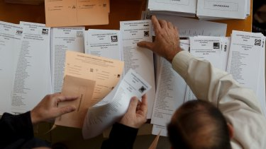 Spanish voters  collect their ballot papers at a polling station in Madrid on Sunday.