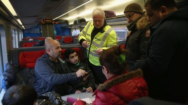 A Danish policeman checks the papers of passengers on a train arriving from Germany following spot checks designed to stem the flow of migrants passing through on their way to Sweden last year.