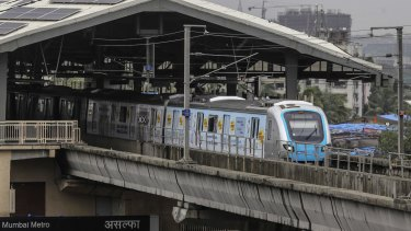 A train travels along a section of elevated track on the Mumbai metro.