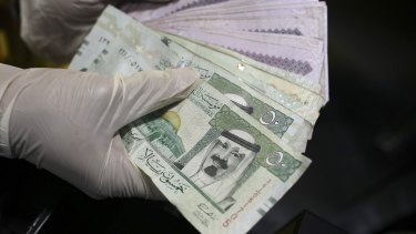 An employee counts a handful of Riyal banknotes from the cash till of a mobile burger van on the side of a highway in Riyadh, Saudi Arabia.