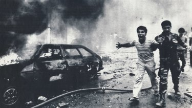 Bystanders are led away after a car bomb blast in Beirut in August 1985.