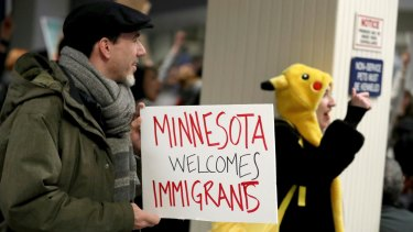 Adrian Hegeman holds a sign while joining other opponents to new immigration restrictions to protest an executive order signed by President Donald Trump.