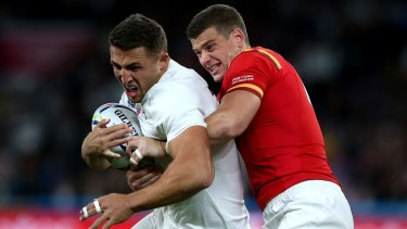 Sam Burgess is tackled by Scott Williams during the match between England and Wales.