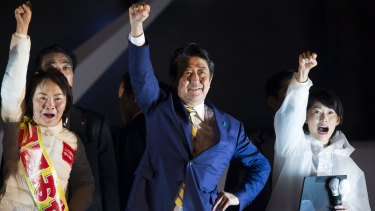 Exit polls say Shinzo Abe's (centre) Liberal Democratic party-led coalition was set to win 311 seats, keeping a majoirty in Japan's lower-house.