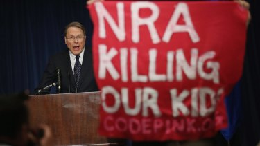 A demonstrator from an anti-gun lobby holds up a banner as NRA executive vice-president Wayne LaPierre speaks at a  news conference after the massacre at Sandy Hook Elementary School in Connecticut.
