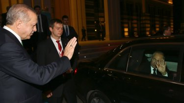 Turkish President Recep Tayyip Erdogan, left, waves goodbye to Russian President Vladimir Putin following their meeting in Ankara.