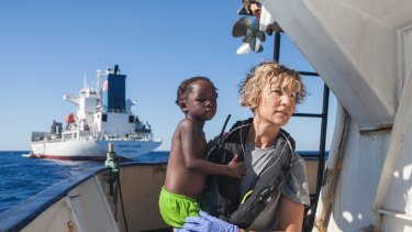 A Spanish nurse of Proactiva Open Arms NGO carries a child rescued from the Mediterranean Sea aboard the Golfo Azzurro ship, operated by Proactiva.