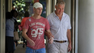 One-punch attack: Michael McEwen leaves hospital with his father, Robert.