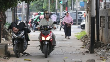 A motorcyclist rests on his bike as another passes him on a footpath in Jakarta on Tuesday.