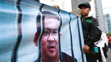 A Muslim protester displays a banner depicting Jakarta governor Ahok behind bars outside court on the day of his trial hearing.