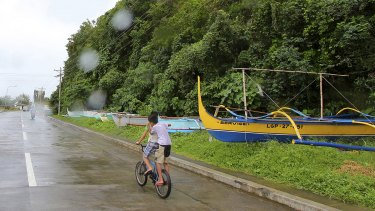 Boys ride a bike past boats placed on a safer area in Legazpi city, central Philippines as Typhoon Melor slammed into the eastern Philippines on Monday.