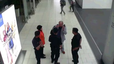 In this image from security camera footage, Kim Jong-nam, in grey, gestures towards his face while talking to airport security at Kuala Lumpur International Airport, shortly before his death.