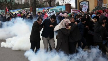 People run as riot police use tear gas and water cannons to disperse a crowd showing their support for the <i>Zaman</i> newspaper in Istanbul.