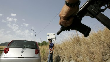 Organised crime is a problem in southern Italy. An Italian police officer holds a sub-machine gun at a roadblock in Calabria.