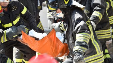 Rescue workers rescue a dead body in a damaged building in Accumuli.