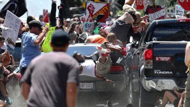 A vehicle drives into a group of protesters demonstrating against a white nationalist rally in Charlottesville, Virginia. Rebel Media's coverage of event drew fire and triggered a wave of condemnation.