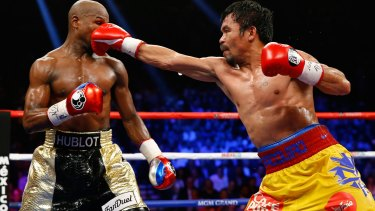 Manny Pacquiao throws a right at Floyd Mayweather during their welterweight unification championship bout in May 2015.