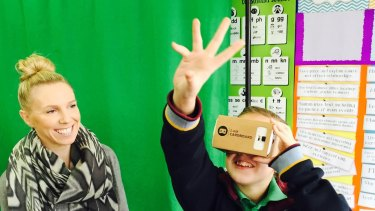 Teacher Sarah Anderson and one of her students with a Google Cardboard viewer.