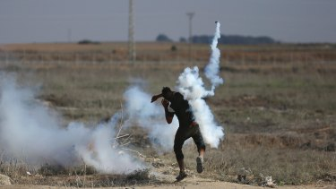 A Palestinian protester throws a teargas canister, originally fired by Israeli soldiers, back during clashes on the Israeli border with the Gaza Strip.