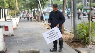 """Alfred Sitorus from the Coalition of Pedestrians in Jakarta holding a placard that says: """"Indonesians are lazy walking because ....?""""."""